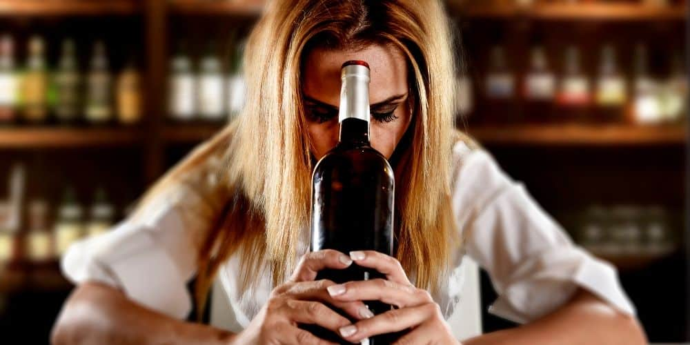 Am I an alcohol? Myths and misconceptions about problem drinking. Woman with wine bottle.