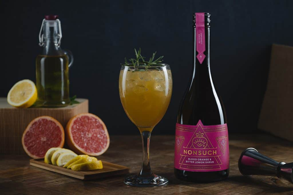A non-alcoholic cocktail in a wine glass, garnished with rosemary with a blood orange cut open next to it and a bottle of Nonsuch Shrubs